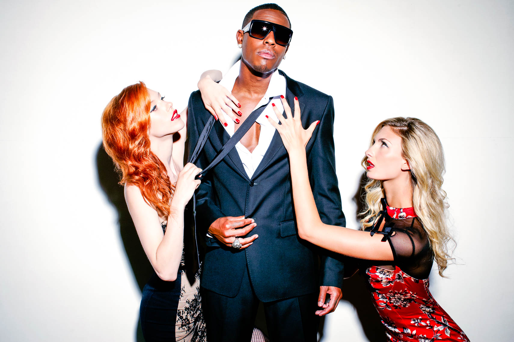 Hyro da hero dressed in a suit and sunglasses with a blonde and a red hair girl hanging off him
