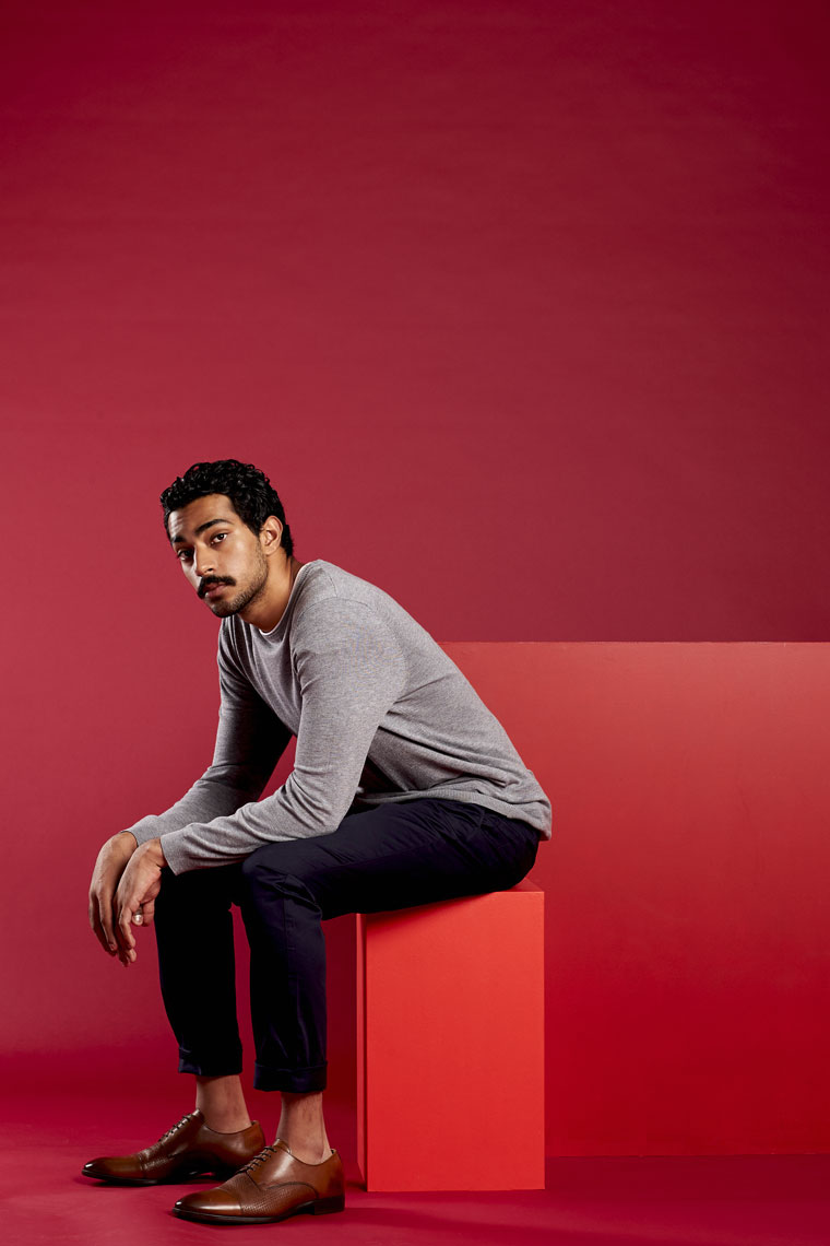 Young man sitting on a red box in a red studio wearing a grey jumper and black trousers