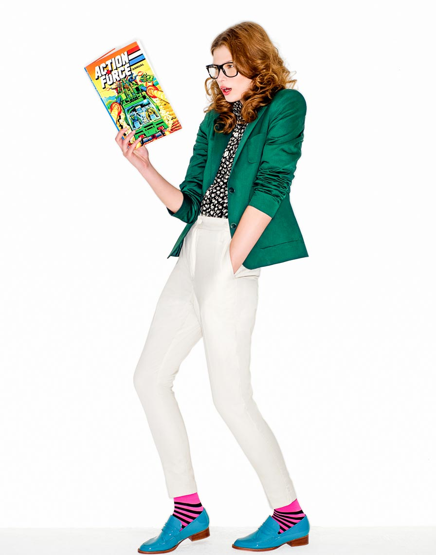 Green blazer and white pants reading a comic