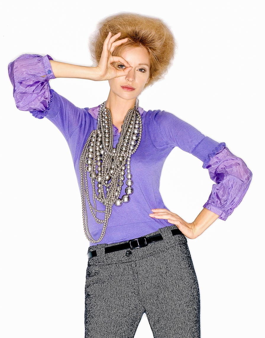 Girl in a purple jumper and pearls with Margaret Thatcher style hair