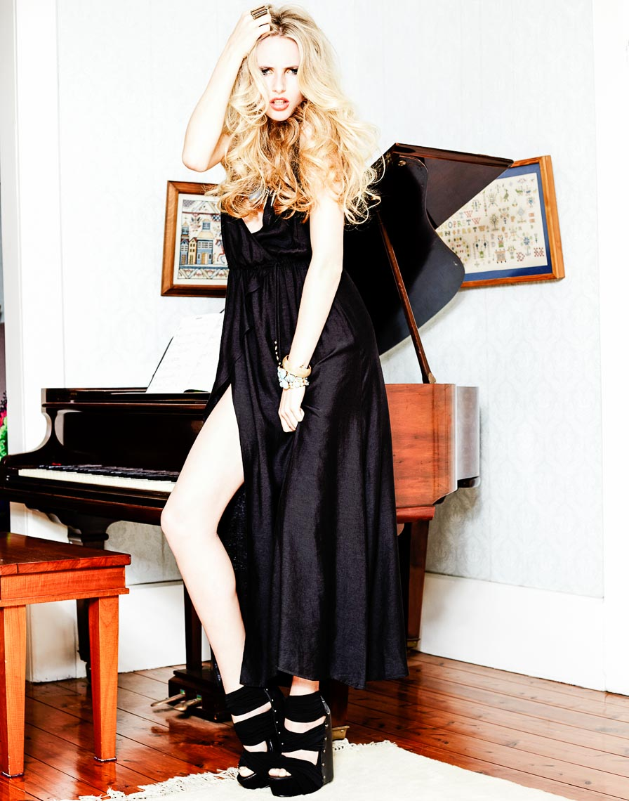 Blonde girl standing in front of a piano