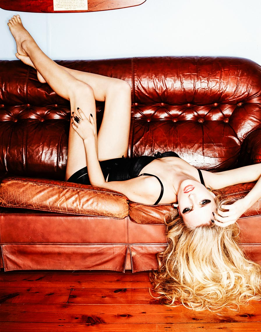 Brown leather sofa with a blonde girl in underwear upside down