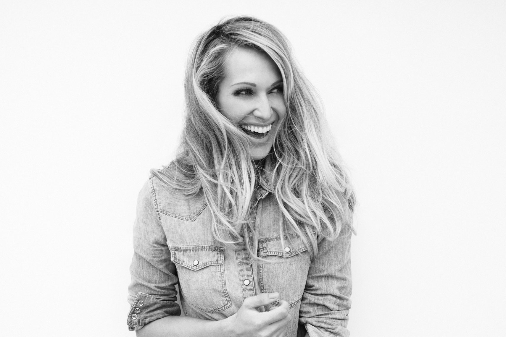 Erika Heynatz laughing in a black and white portrait and a denim shirt